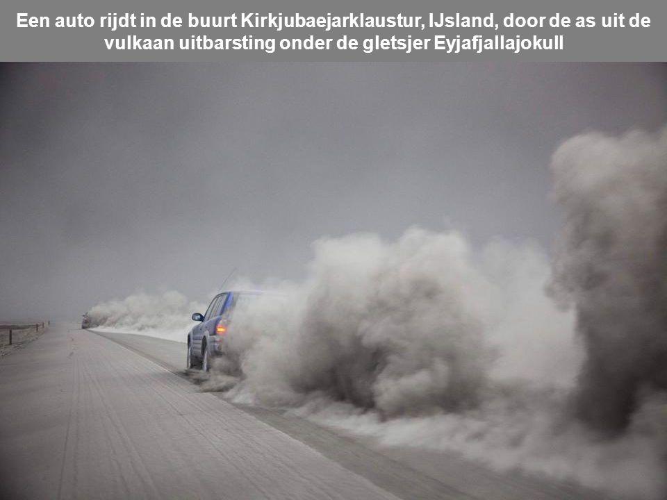 Een boerderij in de buurt van de vulkaan Eyjafjallajokull, rook en as golven tijdens een uitbarsting