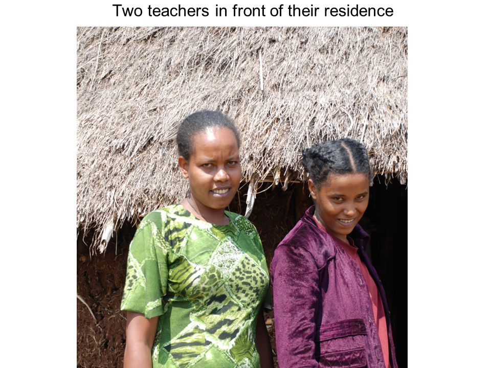Two teachers in front of their residence