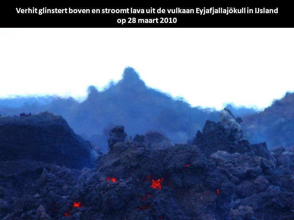 Verhit glinstert boven en stroomt lava uit de vulkaan Eyjafjallajökull in IJsland op 28 maart 2010