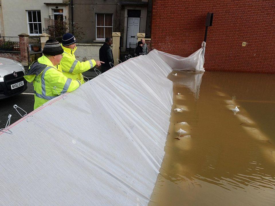 De rivier de Avon in Bristol steeg, mensen maken een ophoging in een straat, gehoopt wordt om het hoge water te stoppen voor het bij de huizen komt