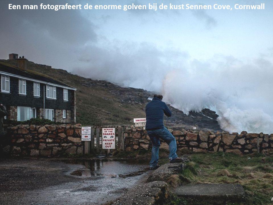 Een man fotografeert de enorme golven bij de kust Sennen Cove, Cornwall
