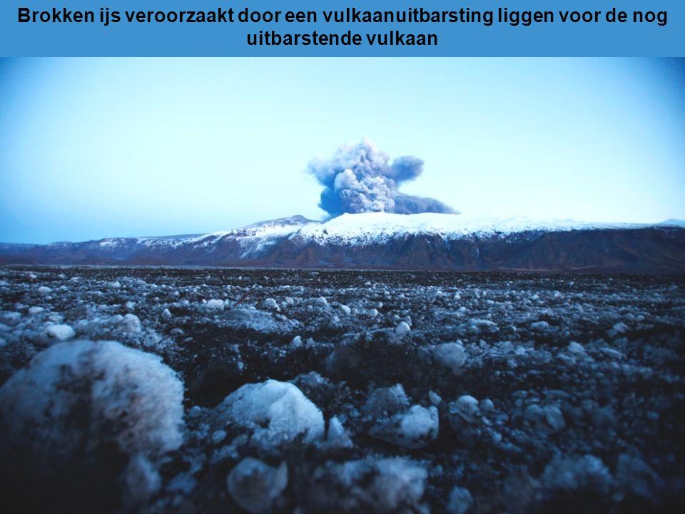 Brokken ijs veroorzaakt door een vulkaanuitbarsting liggen voor de nog uitbarstende vulkaan