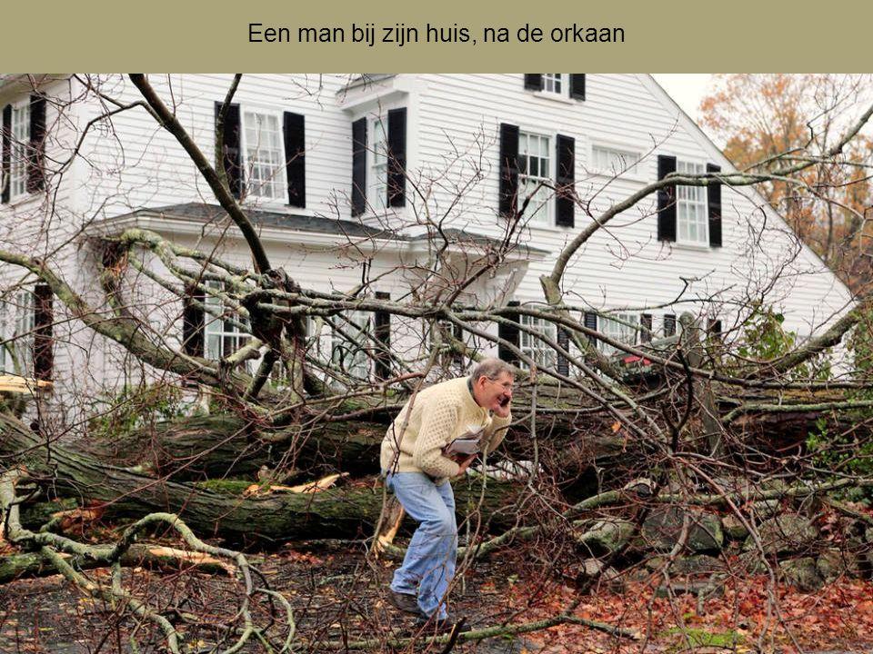Een man bij zijn huis, na de orkaan