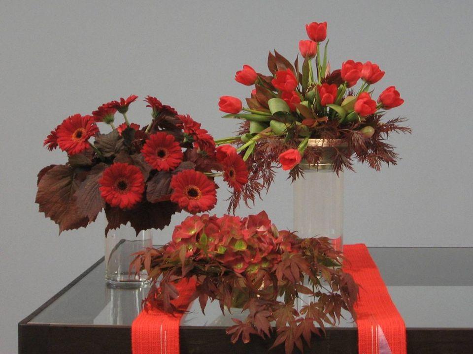We zien drie schalen met rode bloemen en rood blad, de kleur van de Heilige Geest.