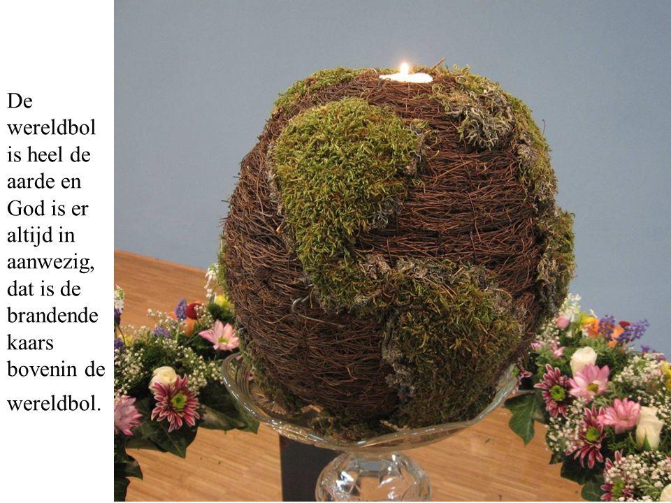 De wereldbol is heel de aarde en God is er altijd in aanwezig, dat is de brandende kaars bovenin de wereldbol.