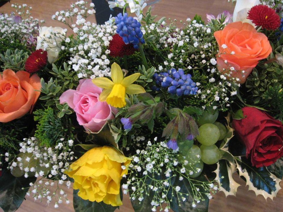 De krans met bloemen rond de wereldbol zijn de mensen en heel de schepping die God alle eer en lof geven om zijn liefde en trouw.