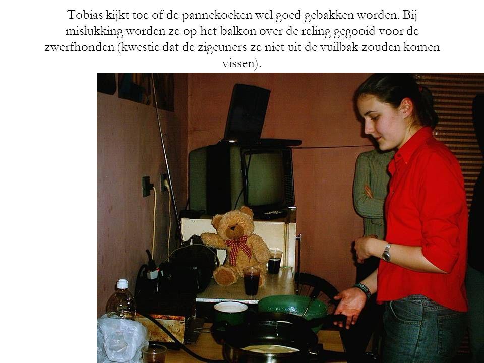 Tobias kijkt toe of de pannekoeken wel goed gebakken worden.