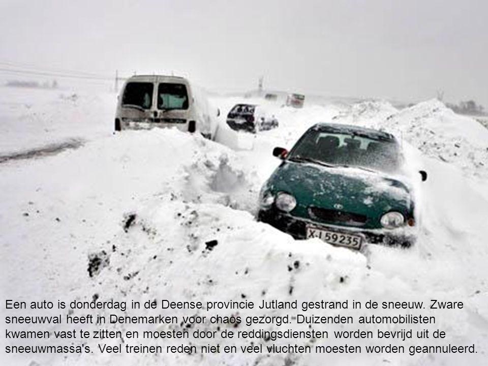 EPA Een auto is donderdag in de Deense provincie Jutland gestrand in de sneeuw. Zware sneeuwval heeft in Denemarken voor chaos gezorgd. Duizenden auto