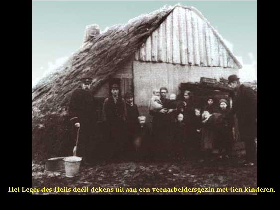Krotten, achterbuurten, sanering: Krotwoning, plaggenhut in Drenthe [Drente], 1936. Een moeder met kind zit in de deuropening van de uit plaggen en pl