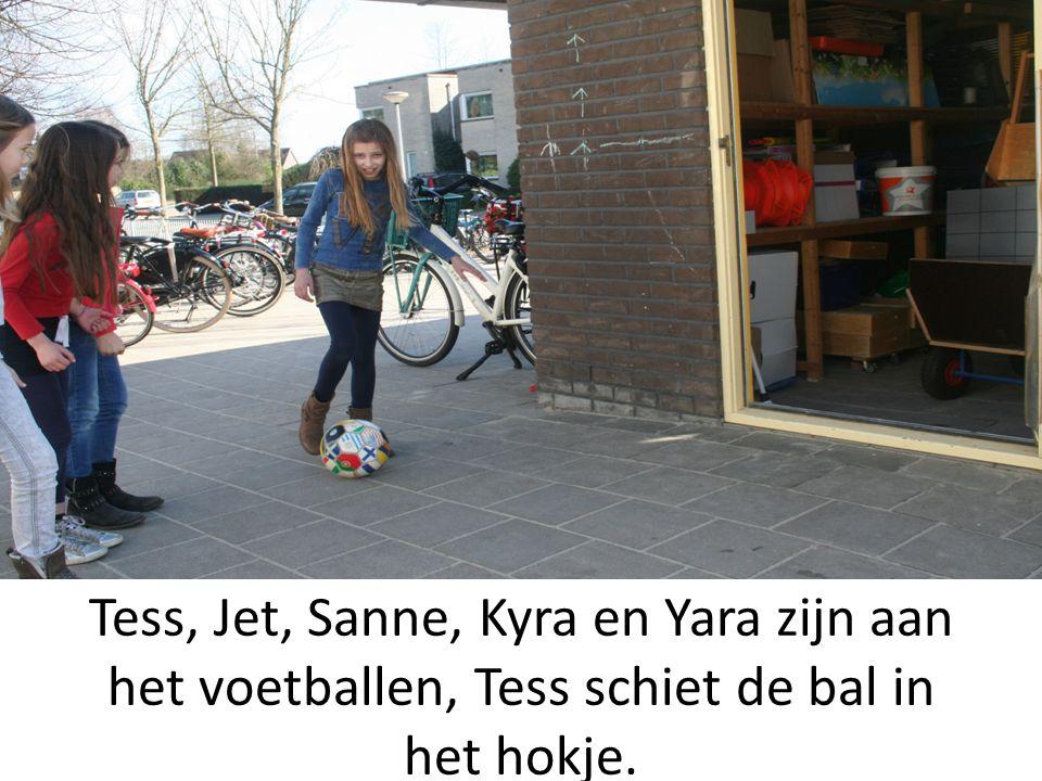 Tess, Jet, Sanne, Kyra en Yara zijn aan het voetballen, Tess schiet de bal in het hokje.