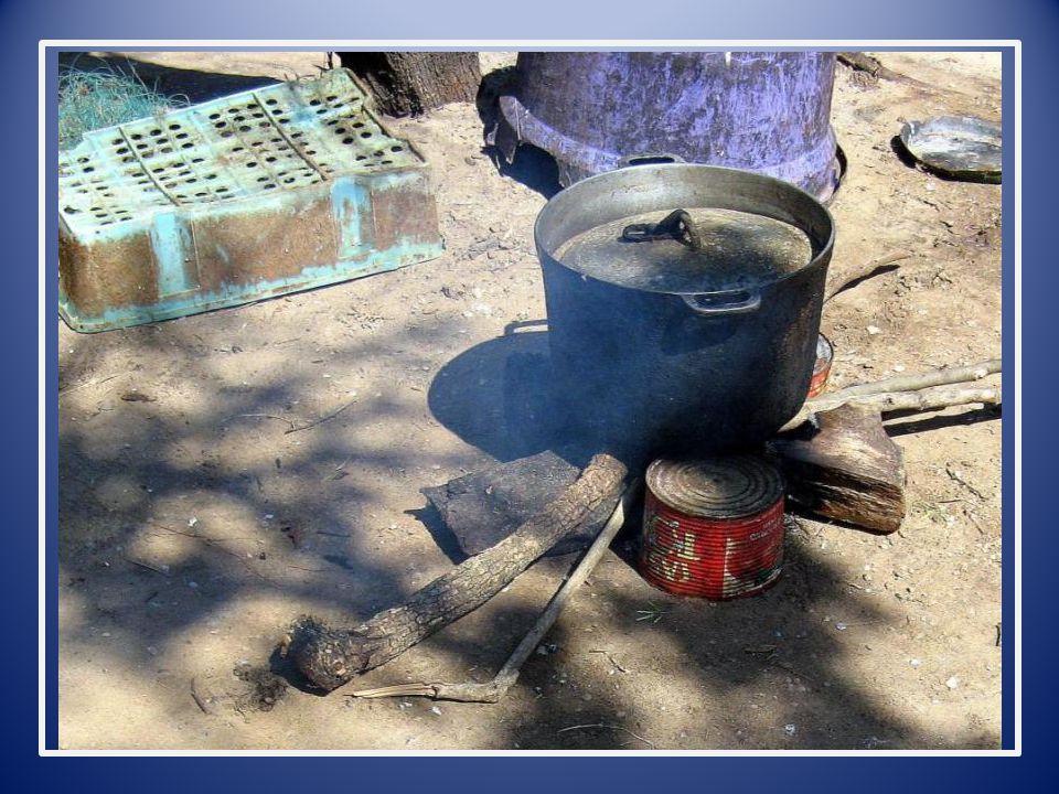 Op het hoofd dragen vrouwen en kinderen bussels hout naar. hun kookpoten en rookovens.