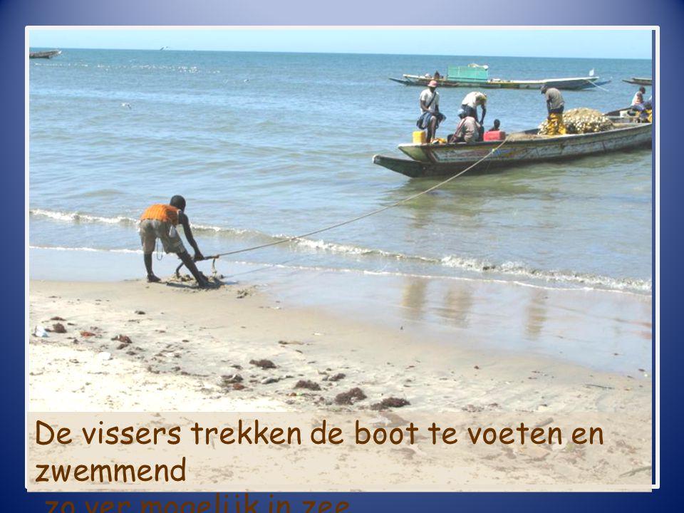 De vissers trekken de boot te voeten en zwemmend zo ver mogelijk in zee.