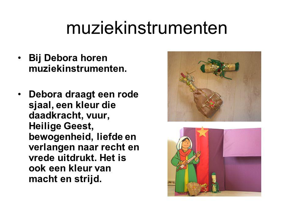 muziekinstrumenten Bij Debora horen muziekinstrumenten. Debora draagt een rode sjaal, een kleur die daadkracht, vuur, Heilige Geest, bewogenheid, lief