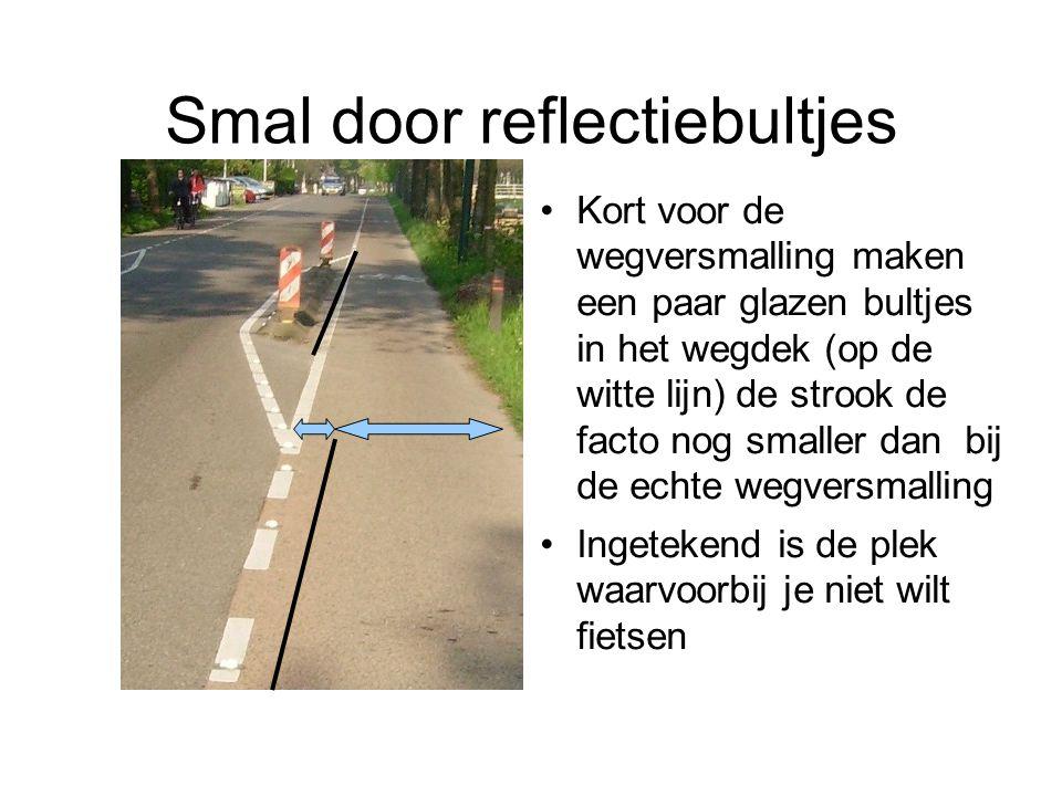 Smal door reflectiebultjes Kort voor de wegversmalling maken een paar glazen bultjes in het wegdek (op de witte lijn) de strook de facto nog smaller d