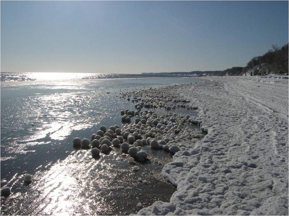 Cientos, miles de bolas de hielo con el corazón de nieve y del tamaño de un balón de fútbol se amontonan a lo largo de la orilla en un espectáculo mar