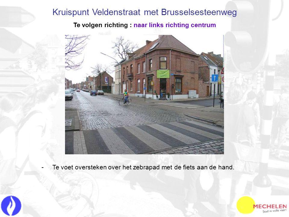 -T-Te voet oversteken over het zebrapad met de fiets aan de hand. Kruispunt Veldenstraat met Brusselsesteenweg Te volgen richting : naar links richtin