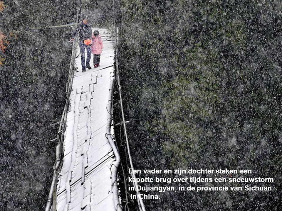 Een vader en zijn dochter steken een kapotte brug over tijdens een sneeuwstorm in Dujiangyan, in de provincie van Sichuan in China.
