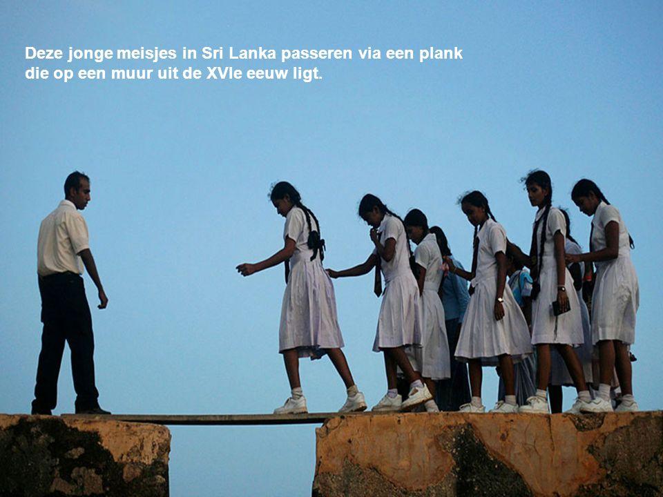 Deze jonge meisjes in Sri Lanka passeren via een plank die op een muur uit de XVIe eeuw ligt.