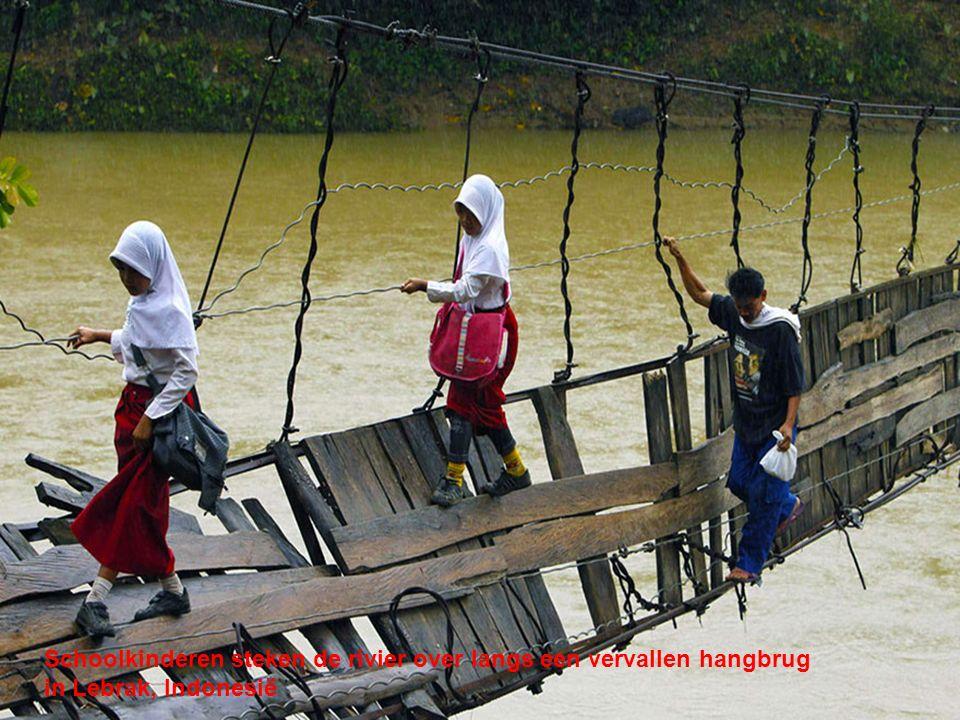 Schoolkinderen steken de rivier over langs een vervallen hangbrug in Lebrak, Indonesië