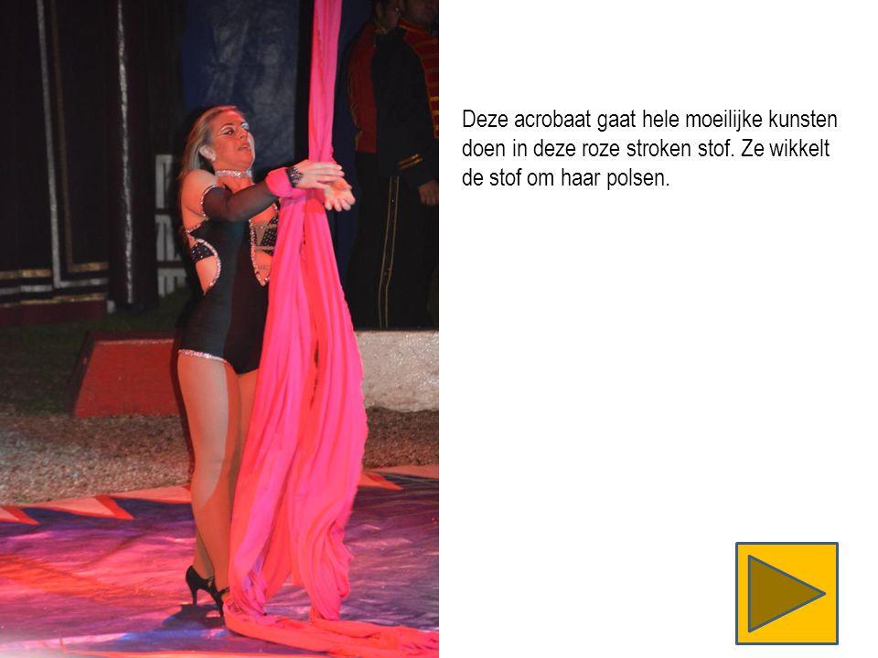 Deze acrobaat gaat hele moeilijke kunsten doen in deze roze stroken stof.