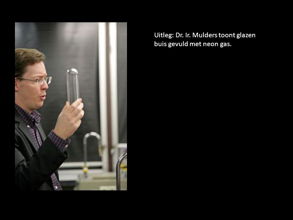 . Uitleg: Dr. Ir. Mulders toont glazen buis gevuld met neon gas.