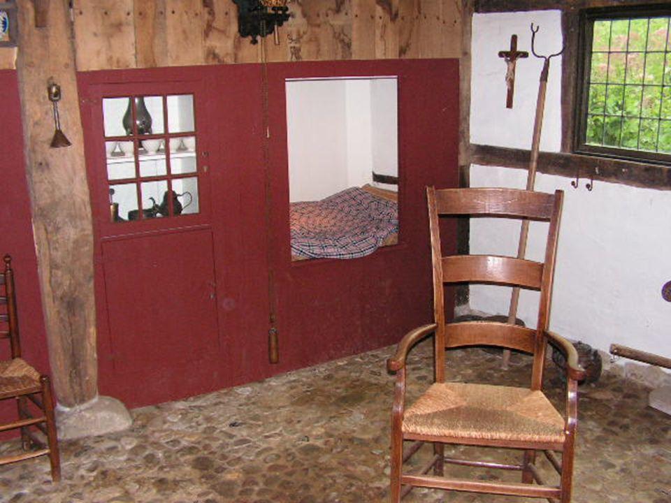 De woonkamer is ingericht zoals een molenaarsgezin woonde rond 1900, met de bedstee en een schouw met fornuis uit die tijd.