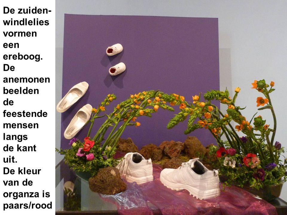 De zuiden- windlelies vormen een ereboog. De anemonen beelden de feestende mensen langs de kant uit. De kleur van de organza is paars/rood