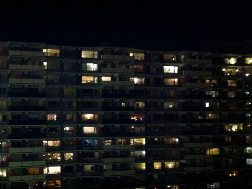 Plaatje rij huizen, waarvan allemaal donker behalve 1.
