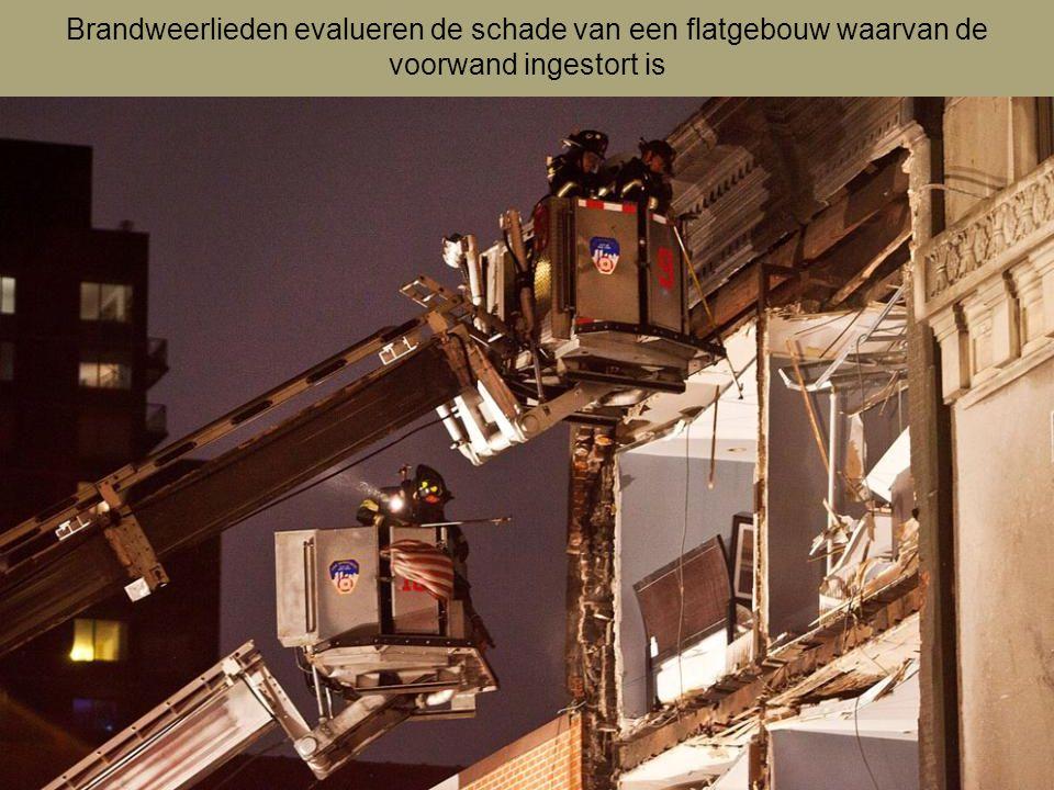 Brandweerlieden evalueren de schade van een flatgebouw waarvan de voorwand ingestort is