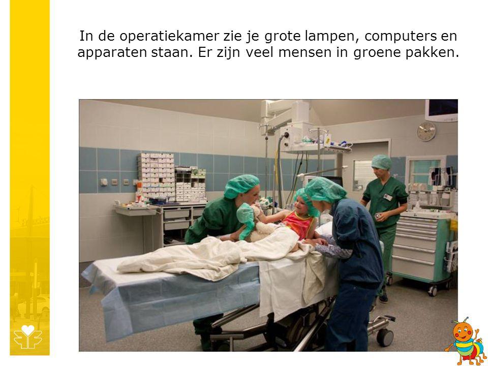 In de operatiekamer zie je grote lampen, computers en apparaten staan. Er zijn veel mensen in groene pakken.
