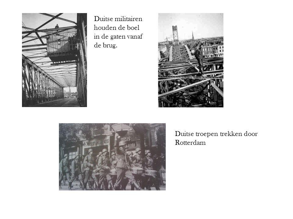 Duitse militairen houden de boel in de gaten vanaf de brug. Duitse troepen trekken door Rotterdam