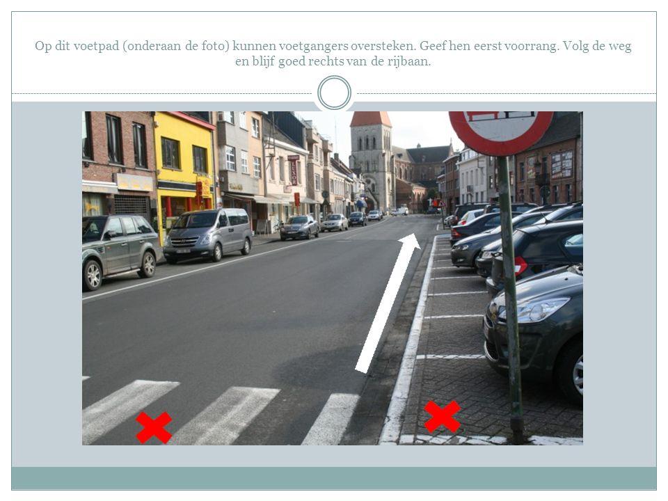 Op dit voetpad (onderaan de foto) kunnen voetgangers oversteken. Geef hen eerst voorrang. Volg de weg en blijf goed rechts van de rijbaan.