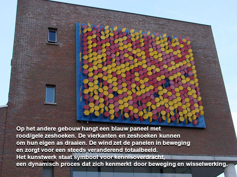 Op het andere gebouw hangt een blauw paneel met rood/gele zeshoeken. De vierkanten en zeshoeken kunnen om hun eigen as draaien. De wind zet de panelen