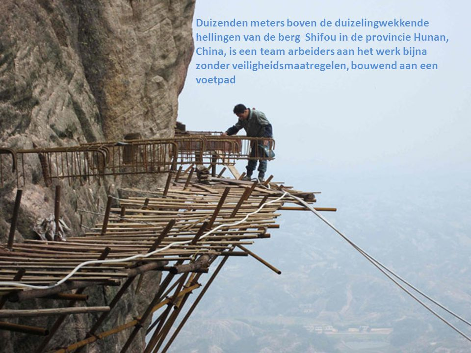 De bouwvakkers bouwen een houten voetpad hangend aan de steile wand van de berg.