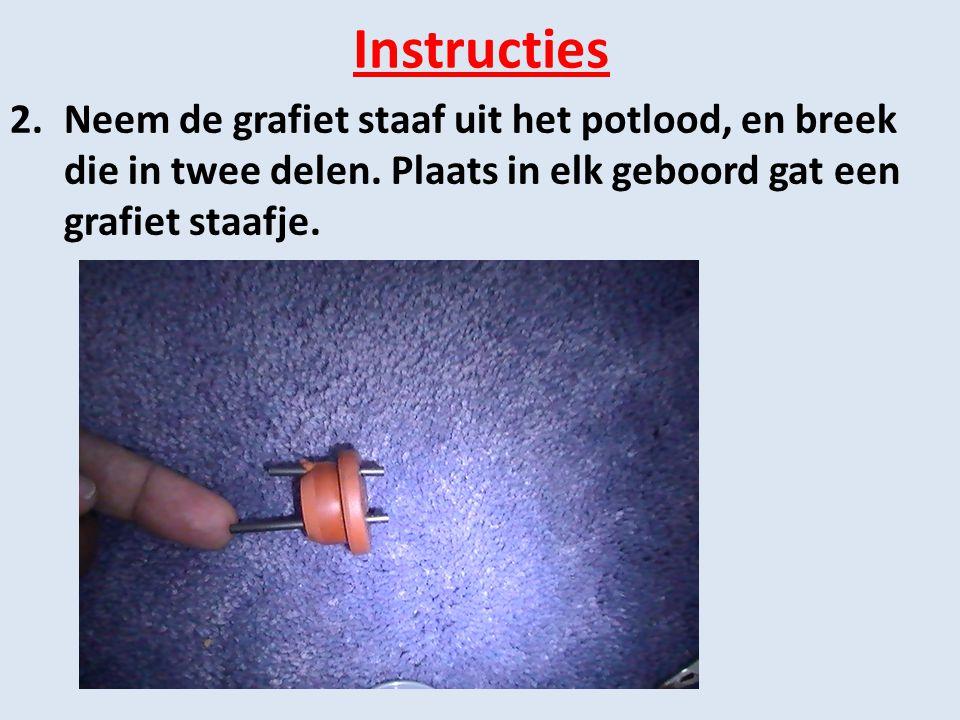 Instructies 2.Neem de grafiet staaf uit het potlood, en breek die in twee delen. Plaats in elk geboord gat een grafiet staafje.