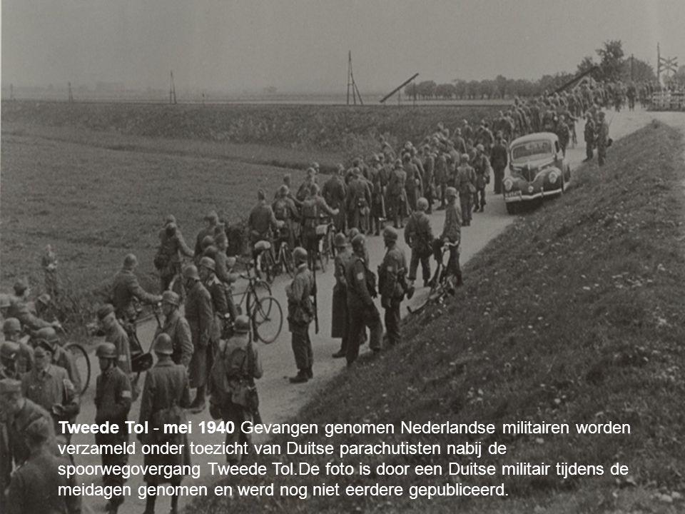 your name Tweede Tol - mei 1940 Gevangen genomen Nederlandse militairen worden verzameld onder toezicht van Duitse parachutisten nabij de spoorwegovergang Tweede Tol.De foto is door een Duitse militair tijdens de meidagen genomen en werd nog niet eerdere gepubliceerd.
