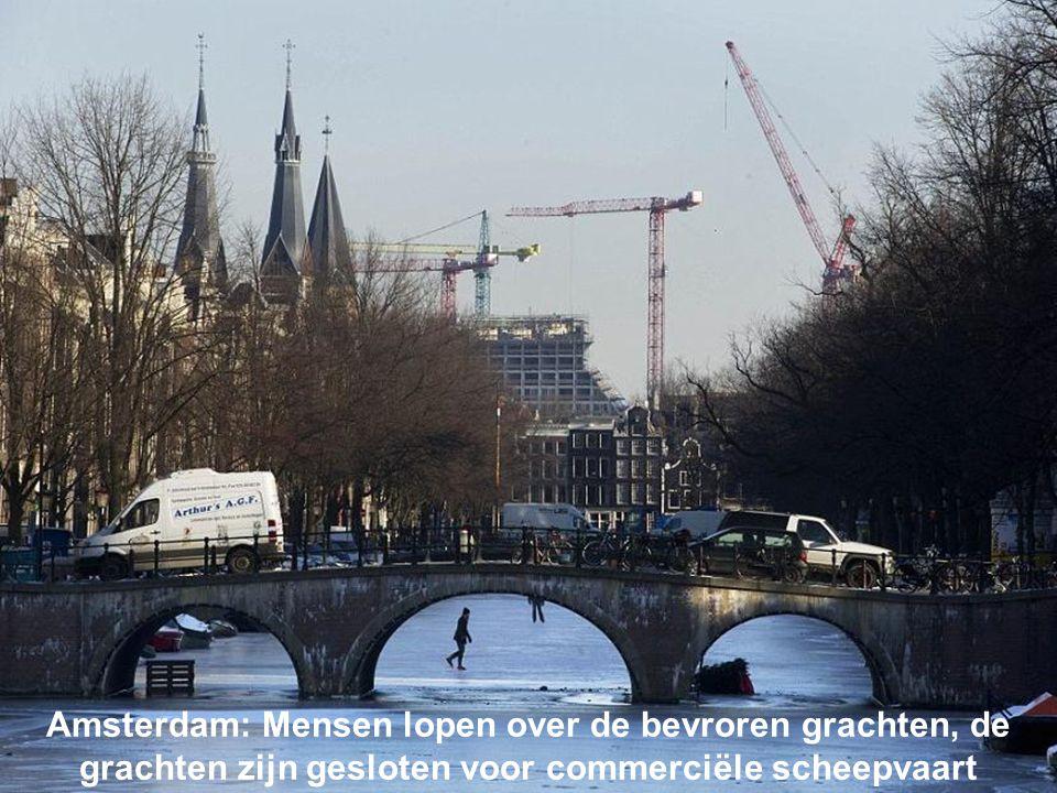 Amsterdam: Mensen lopen over de bevroren grachten, de grachten zijn gesloten voor commerciële scheepvaart