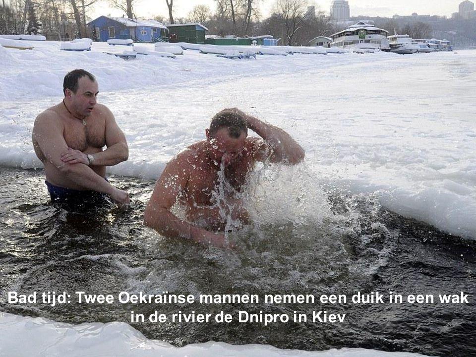 Bad tijd: Twee Oekraïnse mannen nemen een duik in een wak in de rivier de Dnipro in Kiev