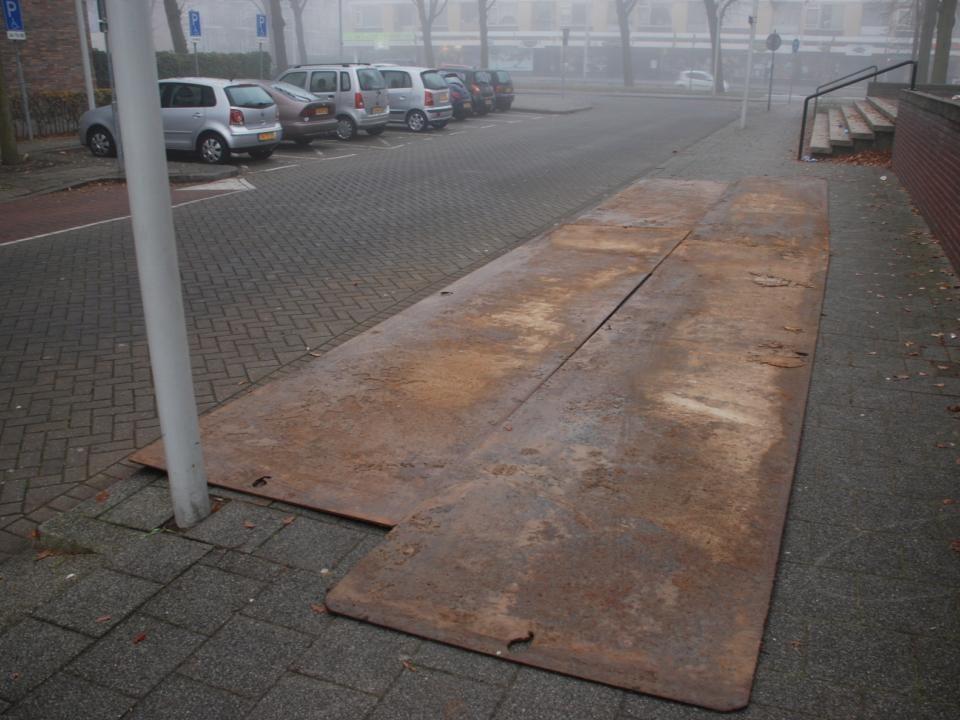 IJzeren rijplaten werden op het trottoir geplaatst voor bescherming