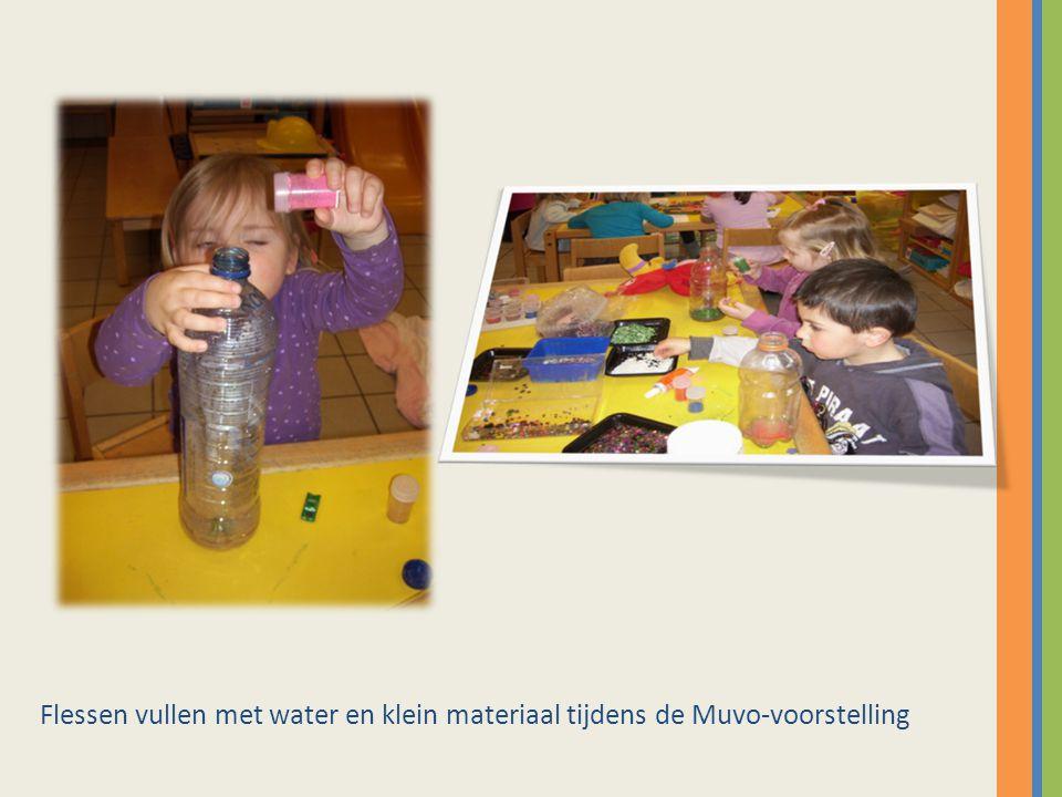 Flessen vullen met water en klein materiaal tijdens de Muvo-voorstelling