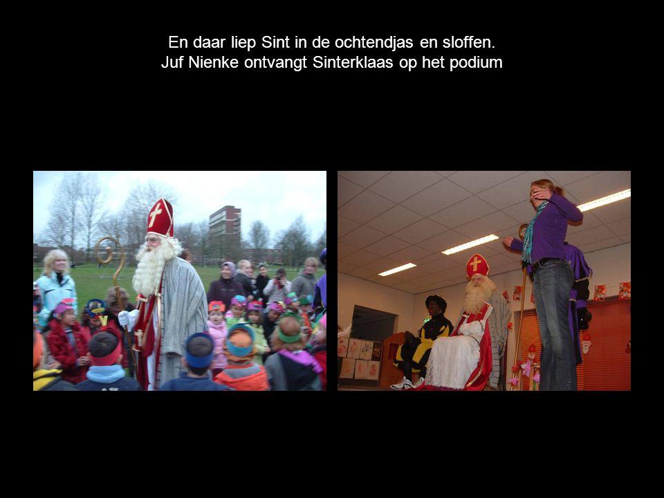 En daar liep Sint in de ochtendjas en sloffen. Juf Nienke ontvangt Sinterklaas op het podium