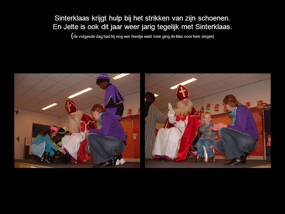 Sinterklaas krijgt hulp bij het strikken van zijn schoenen.