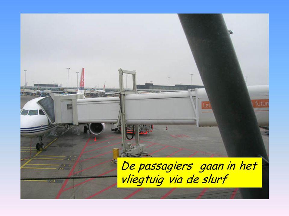De passagiers gaan in het vliegtuig via de slurf