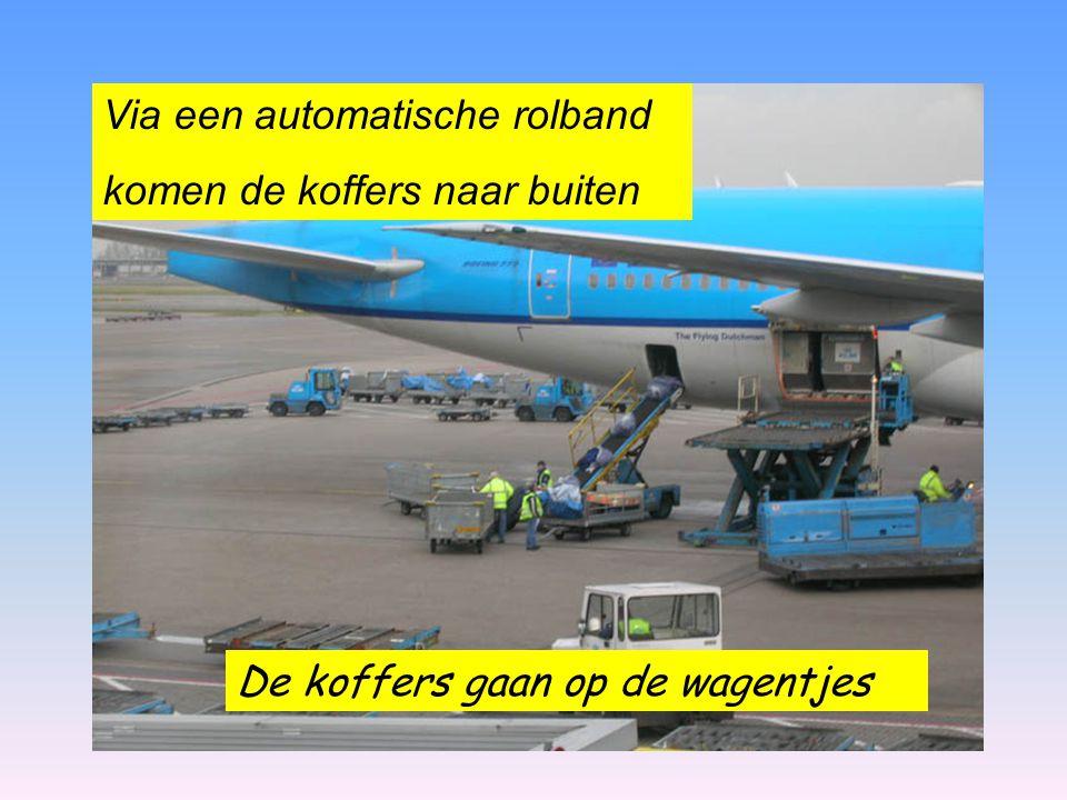 De koffers gaan op de wagentjes Via een automatische rolband komen de koffers naar buiten