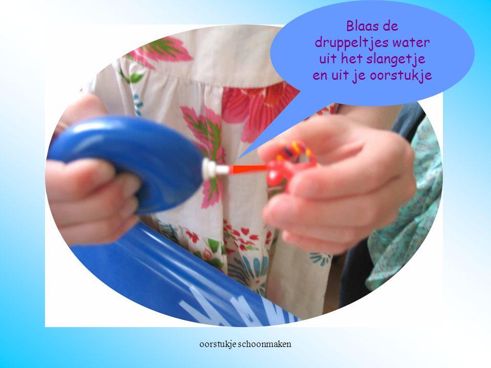 oorstukje schoonmaken Doorblazen Blaas de druppeltjes water uit het slangetje en uit je oorstukje