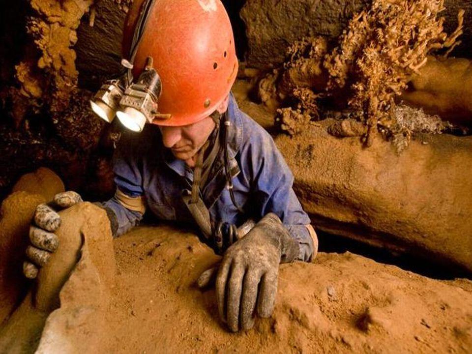 Een speleoloog in actie. Vaak moeten speleologen door zéér enge doorgangen kruipen.