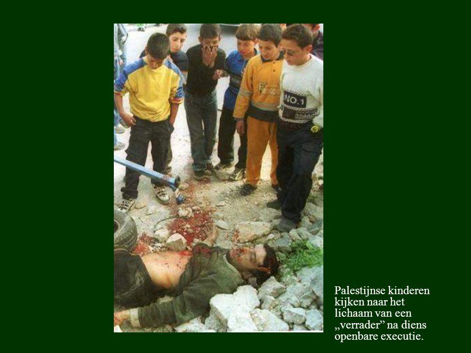"""Palestijnse kinderen kijken naar het lichaam van een """"verrader"""" na diens openbare executie."""