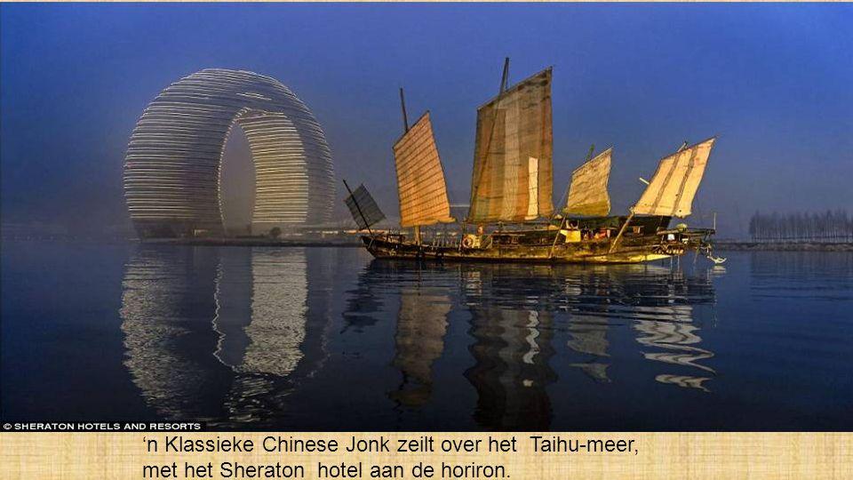 'n Klassieke Chinese Jonk zeilt over het Taihu-meer, met het Sheraton hotel aan de horiron.