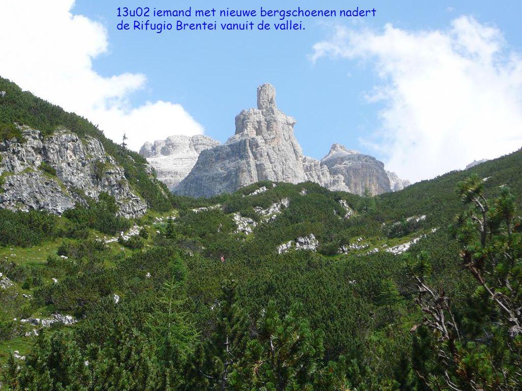 13u02 iemand met nieuwe bergschoenen nadert de Rifugio Brentei vanuit de vallei.