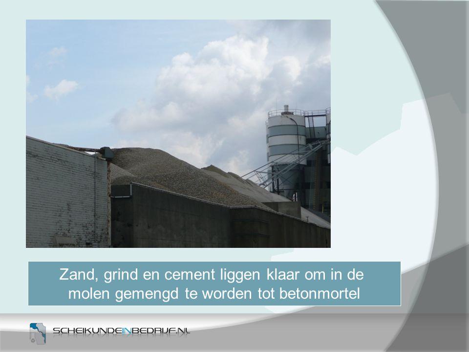 Zand, grind en cement liggen klaar om in de molen gemengd te worden tot betonmortel